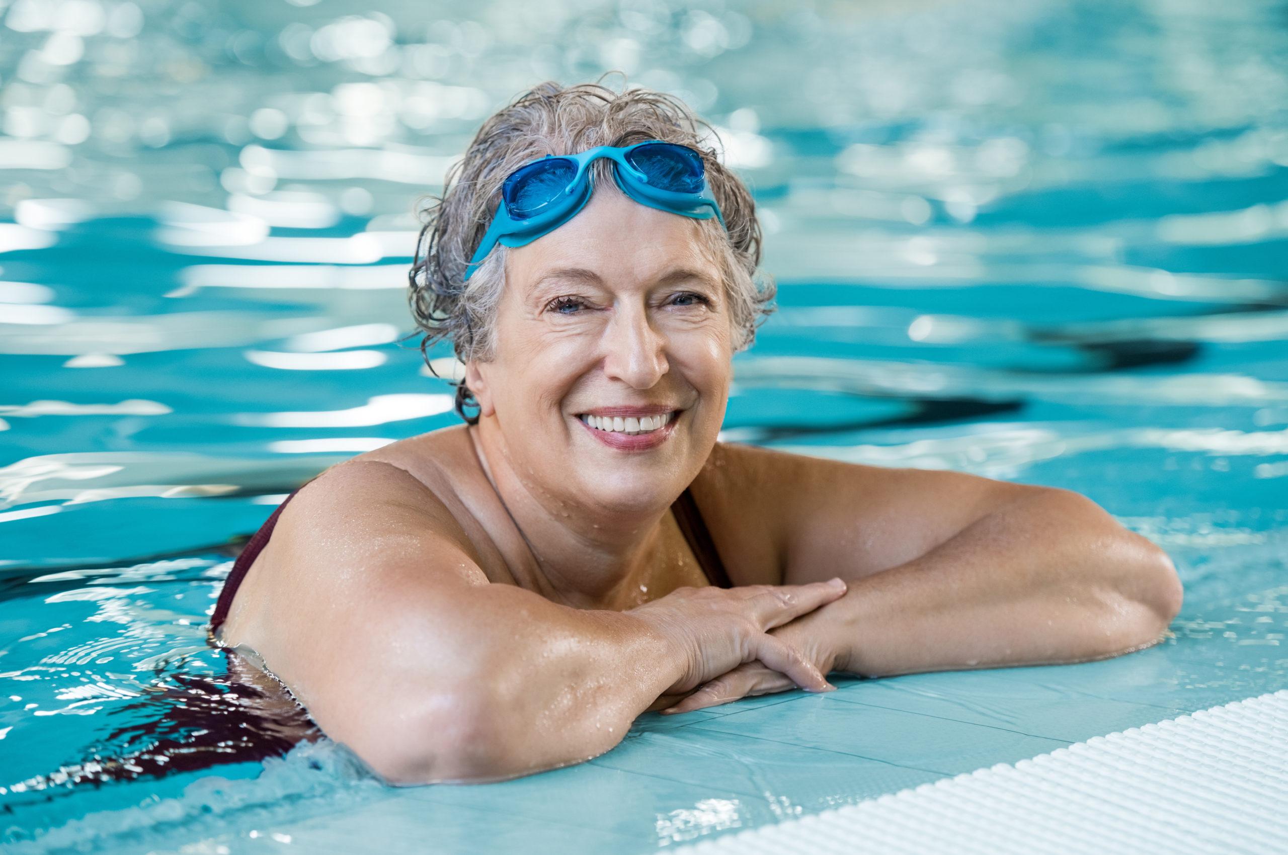Senior woman in pool resting on edge