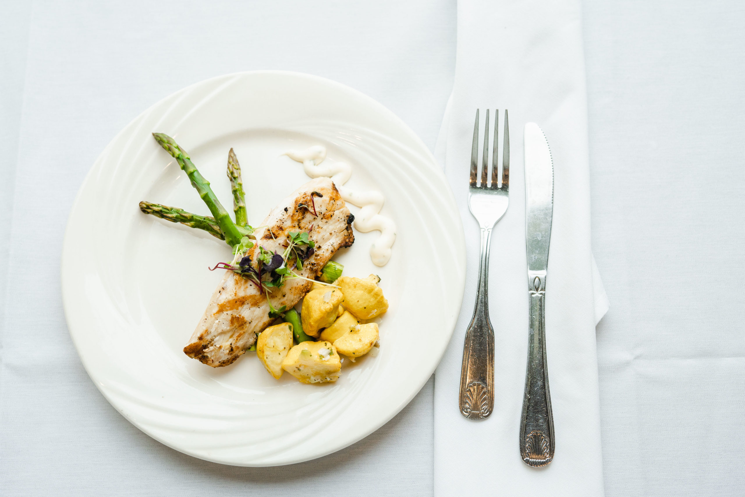 View fo elegantly plated meal with fish, potatoes and asparagus