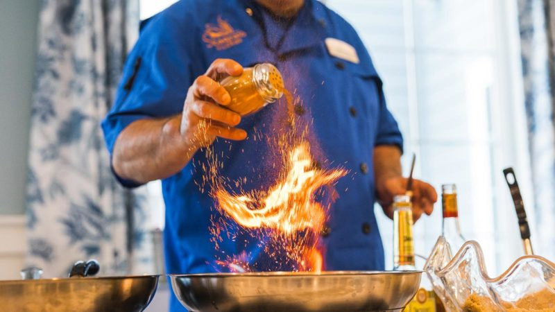 Seagrass Village chef flambéing food for residents