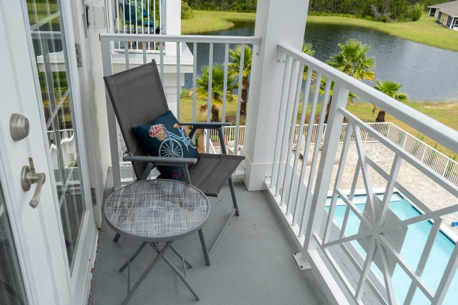 Independent Living Apartment Balcony Overlooking Pool And Pond In Background At Seagrass Village Of Panama City Beach