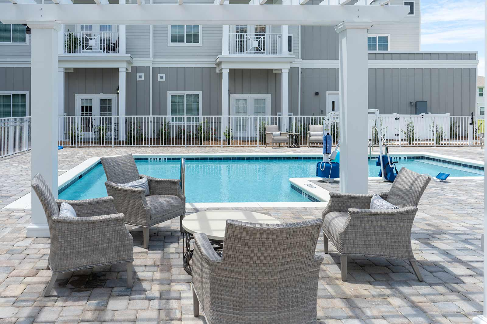 Patio Seating Under Pergola With Swimming Pool In Background At Seagrass Village Of Panama City Beach